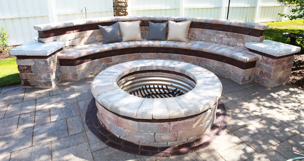 Outdoor stone lounge area with circular brick fire pit | Hittle Landscaping