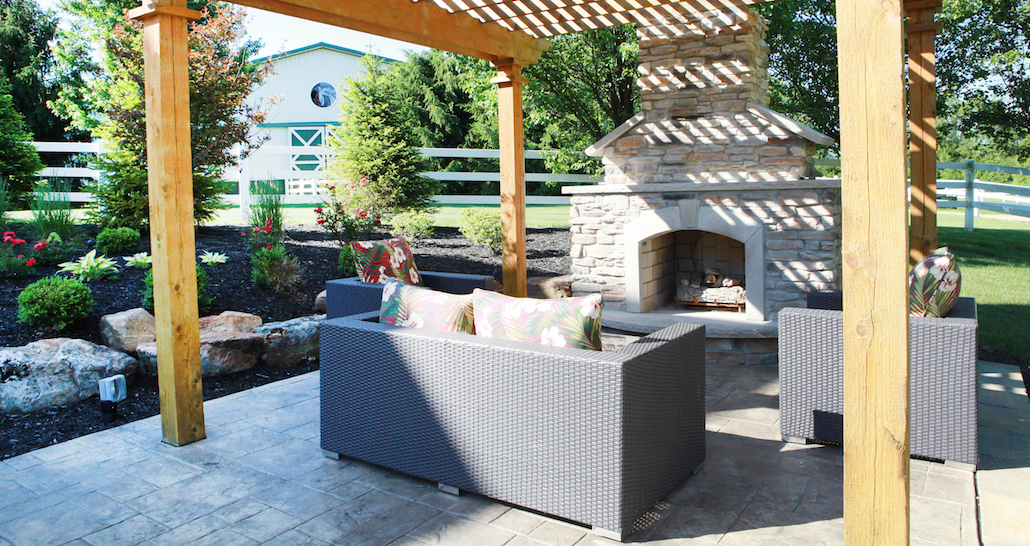 Stone outdoor fireplace with patio furniture | Hittle Landscaping