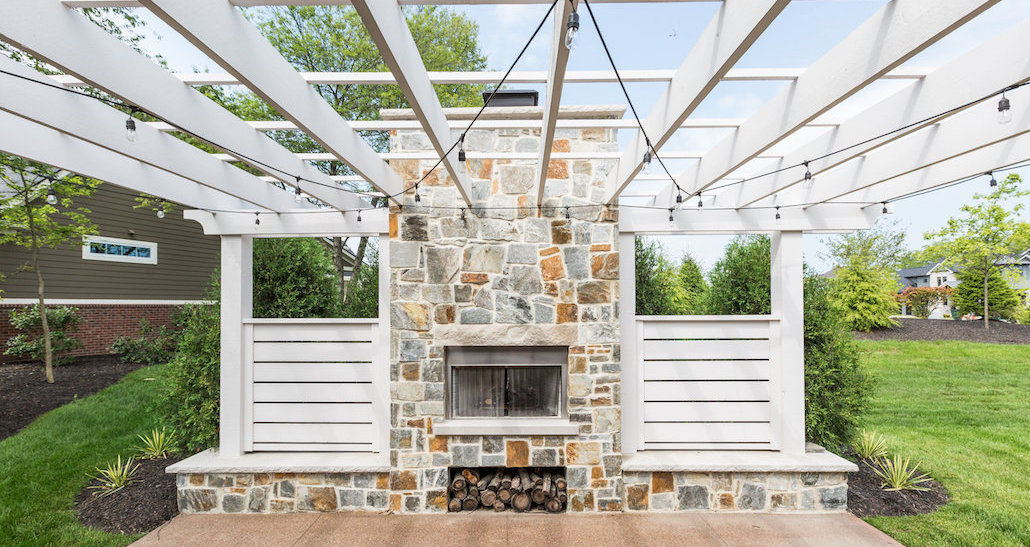 Fireplace with firewood and custom stone masonry | Hittle Landscaping