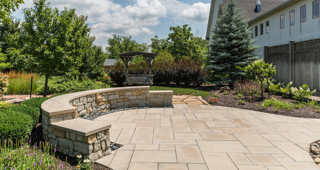 Stone patio with covered swing and sitting area | Hittle Landscaping