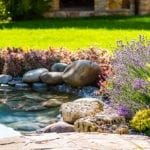Hardscaped walkway leading up to a small pons with rocks, shrubbery and flowers | Landscaping Blogs | Hittle Landscaping