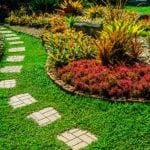 Yard with green grass, plants, paving stones, and flower beds | New, Chic Garden Paths in Your Backyard Landscape Design | Hittle Landscape