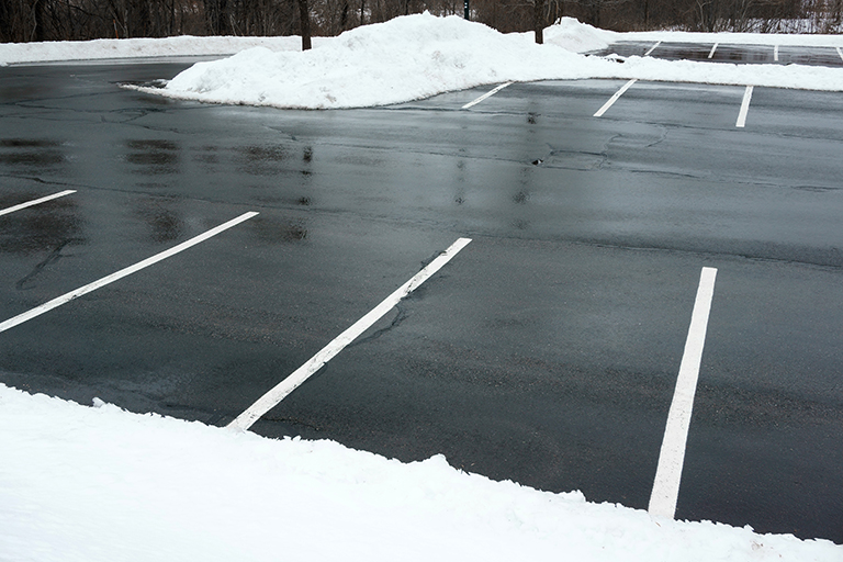 Piles of white snow plowed from blacktop asphalt parking lot | Plan Your Commercial Landscaping Company Projects for 2019 | Hittle Landscape
