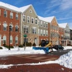 Row of brick and wood townhouse condos along street being plowed of piles of snow   Winter Landscape Tips for Indiana HOA Boards   Hittle Landscape