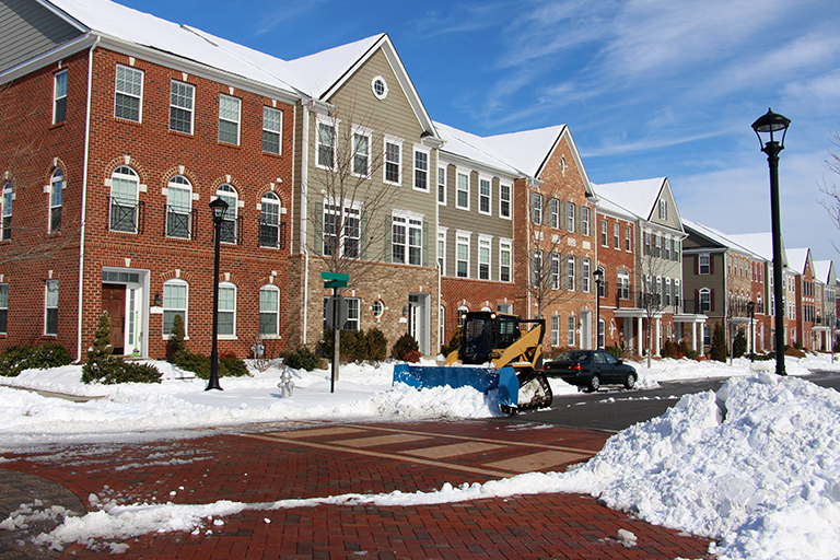 Row of brick and wood townhouse condos along street being plowed of piles of snow | Winter Landscape Tips for Indiana HOA Boards | Hittle Landscape