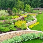 Backyard garden with flowers, trees, green grass, and rock retaining wall | Consider Starting Your New Backyard Landscape Design Ideas This Winter | Hittle Landscape