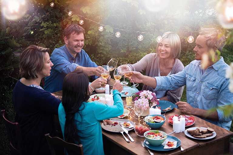 people toasting outdoor dinner | Party Host's Guide to Backyard Landscape Design in Indianapolis | Hittle Landscaping